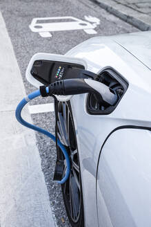 Electric car gettig charged at an charging station - MAMF00777
