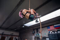 Young woman training, climbing up exercise rope in gym, low angle view - CUF52052