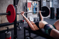 Young woman training, lying on weights bench in gym preparing to lift barbell - CUF52061