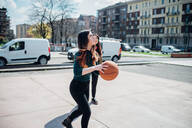 Young female friends playing basketball on city court - CUF52067