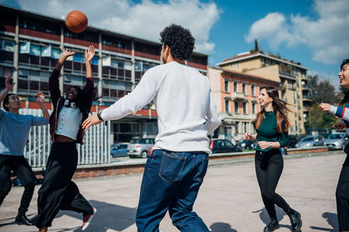 Young female and male adult friends playing basketball on city court - CUF52070