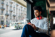 Young man looking at smartphone in cafe window seat - CUF52103