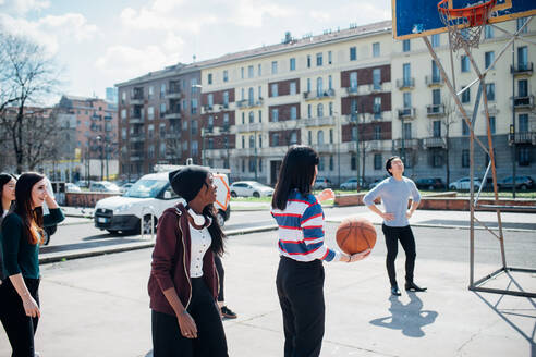 Young female and male adult friends playing basketball on city court - CUF52115