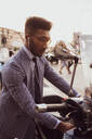 Businessman starting motorcycle on pavement - CUF52172