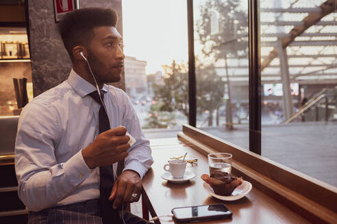 Businessman using smartphone at tea time in cafe - CUF52232