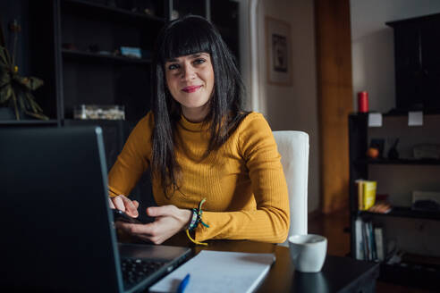 Woman using smartphone in home office - CUF52262