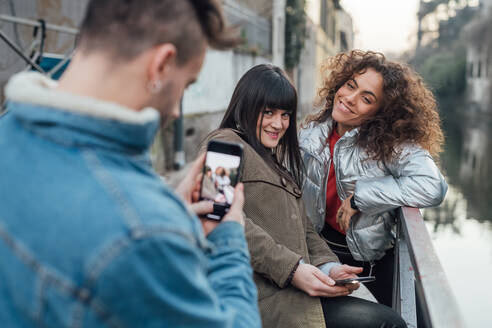 Friends taking photograph by river, Milano, Lombardia, Italy - CUF52286