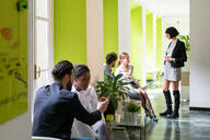 Young male and female business creatives having meetings in open plan office - CUF52343