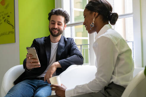 Two male and female business creatives looking at smartphone in office - CUF52346
