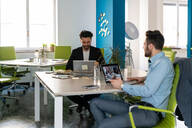 Two male business creatives using laptops at office desk - CUF52349