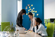 Young female business creative team having sticky notes brainstorm meeting at desk in open plan office - CUF52361