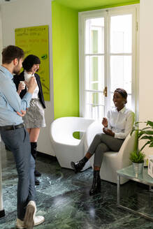 Male and female business creatives taking a break and chatting in office - CUF52367