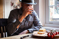Man drinking wine and eating mediterranean food in cafe - CUF52388