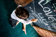 Boy in school uniform writing on blackboard at home - CUF52391