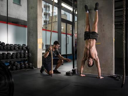 Man motivating friend doing handstand in gym - CUF52397