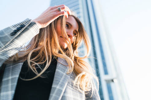 Young woman with long blond hair in front of skyscraper, low angle view, Turin, Piemonte, Italy - CUF52418