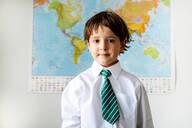 Portrait of boy in school uniform, World map in background - CUF52421