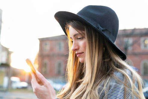 Stylish young woman with long blond hair looking at smartphone on city street - CUF52430
