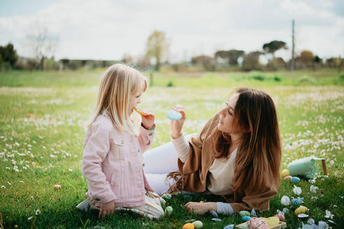 Mother and daughter relaxing in wildflower field after easter egg hunt, Arezzo, Tuscany, Italy - CUF52472
