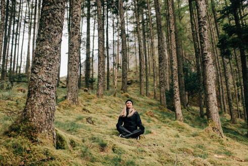 Trekker meditating in forest, Trossachs National Park, Canada - CUF52502