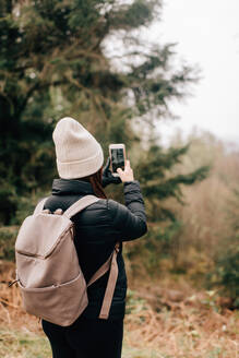 Trekker taking photo, Trossachs National Park, Canada - CUF52505