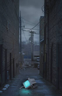 Glowing television in abandoned urban alleyway - BLEF07957