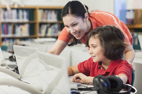 Teacher and student using laptop in library - BLEF08059
