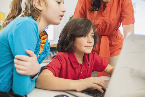 Teacher and children using laptop in library - BLEF08062