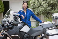 Portrait of smiling young woman leaning on motorcycle in driveway - JUIF01720
