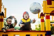 Caucasian boys throwing ball in playground - BLEF08118