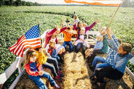 Caucasian family waving American flags on hay ride - BLEF08199