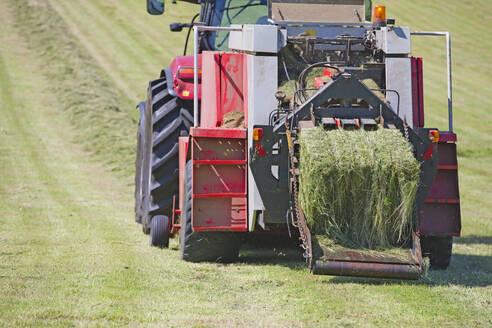 Tractor baling hay in field - JUIF01830
