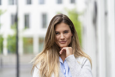 Portrait of young businesswoman, office building in the background - DIGF07091