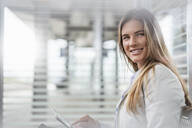 Young businesswoman using tablet in a waiting area - DIGF07136
