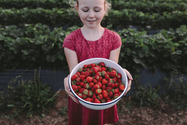High angle view of smiling girl with fresh strawberries in bowl against plants - OGF00002