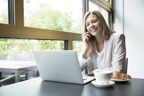 Businesswoman using laptop in a cafe - MFRF01327