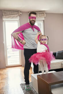 Father and daughter playing superhero and superwoman - ZEDF02485
