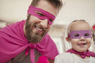 Father and daughter playing superhero and superwoman - ZEDF02488