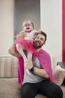 Father and daughter playing superhero and superwoman - ZEDF02503