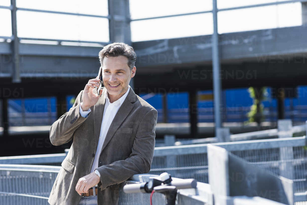 Businessman using smartphone, E-Scooter leaning on railing - UUF18161 - Uwe Umstätter/Westend61