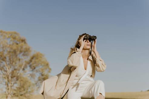 Female traveller looking through binoculars - ERRF01575