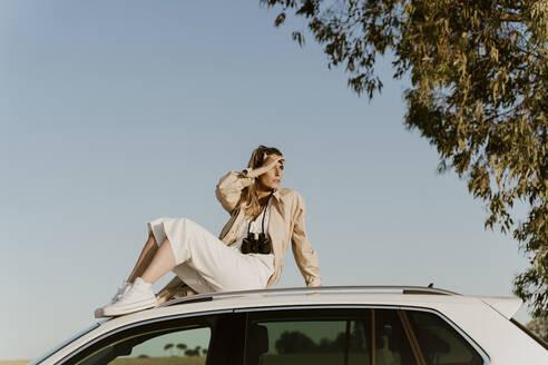 Female traveller sitting on white car roof - ERRF01602