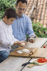Father and son preparing pizza together - ALBF00911