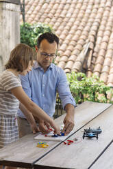 Father teaching his daughter electronics and robotics - ALBF00929