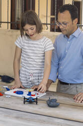 Father teaching his daughter electronics and robotics - ALBF00932