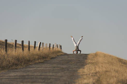 Mid distance view of mature man doing headstand on road against clear sky - KJF00319
