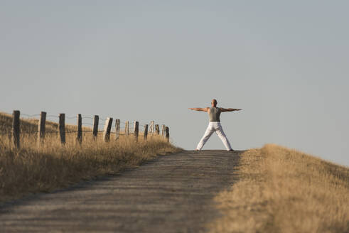 Mid distance view of mature man exercising on road against clear sky - KJF00322