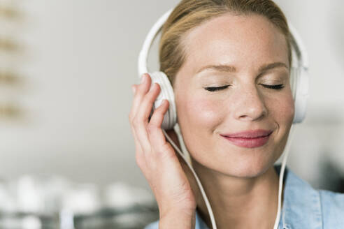 Blond woman in coffee shop with headphones, listening music - JOSF03385