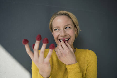Blond woman with raspberries on her fingers, laughing - JOSF03409