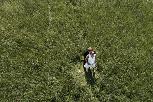 Aerial view of pregnant bride with her husband on a meadow - HMEF00483